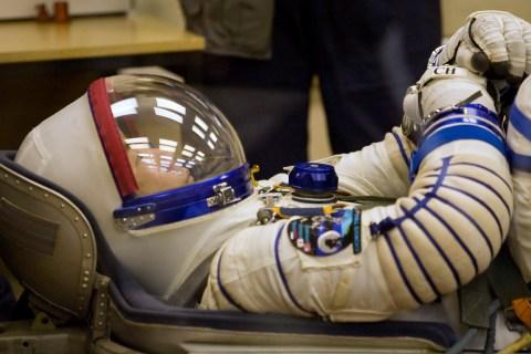 Japan Aerospace Exploration Agency astronaut Soichi Noguchi waits while ground personnel check his space suit at the Baikonur cosmodrome