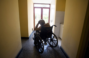 An elderly women rests on her wheel chair in a hall of the senil dementia building of the Canevaro old people's home in Lima