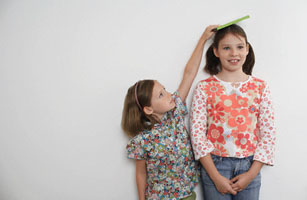 Girl Measuring Big Sister's Height