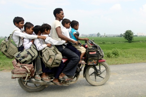 A man rides a motorcycle carrying six children on their way back home from school at Greater Noida in the northern Indian state of Uttar Pradesh
