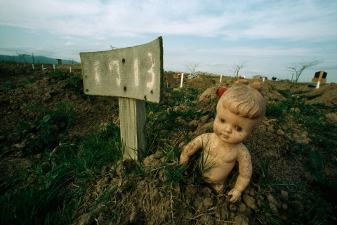 A doll marks the grave of a child