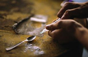 Person preparing syringe of crack cocaine