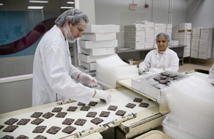 Workers oversee a chocolate line at the Harry & David factory in Medford