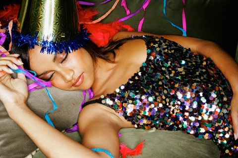 Young mixed race woman sleeping on couch at party