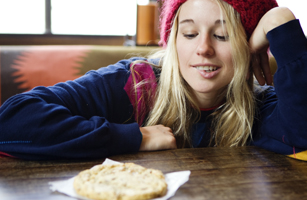 Young woman looks at a big cookie.