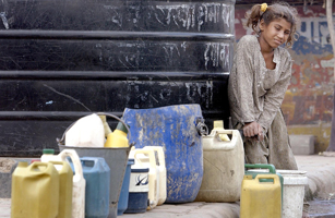 A girl collects drinking water from a tank at a sl