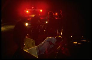 Medics wheeling stretcher fr. ambulance