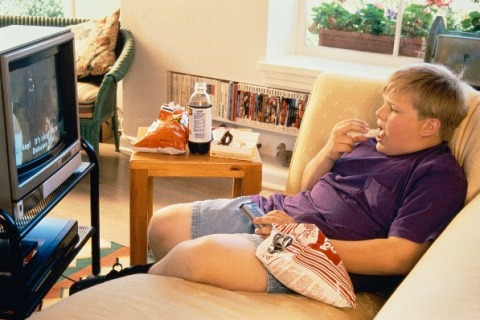 Boy eating junk food in front of TV