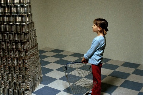 Girl standing next to stack of canned food
