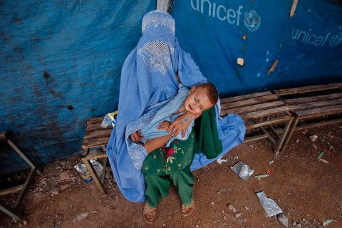 An Afghan refugee woman waits her turn to receive a drop of polio vaccine for her child at the United Nations High Commissioner for Refugees (UNHCR) supported Jalozai camp on the outskirts of Peshawar