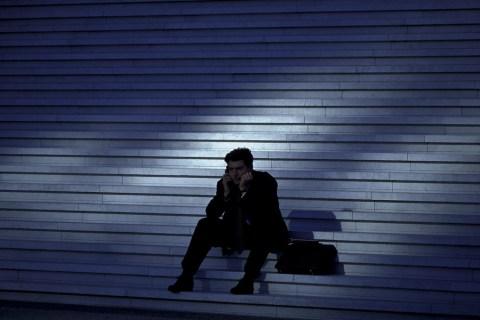 Worried businessman sitting on stairway, outdoors