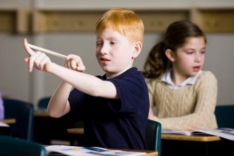 Boy with slingshot in classroom