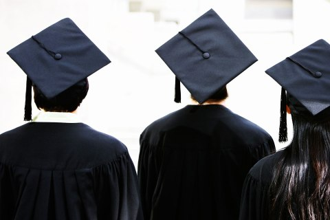 image: Rear view of graduates in caps and gowns