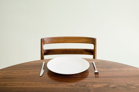 image: Empty plate with knife and fork on table