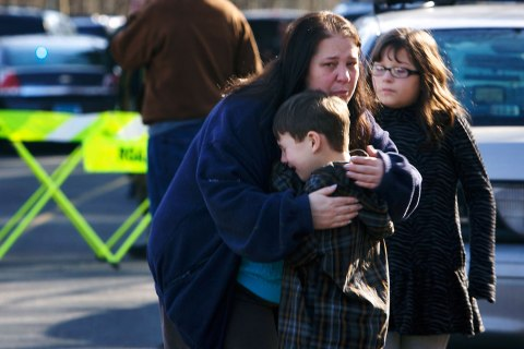 image: A young boy is comforted outside Sandy Hook Elementary School after a shooting in Newtown, Conn., Dec. 14, 2012.