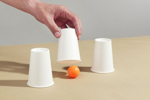 Man lifting paper cup to reveal ball