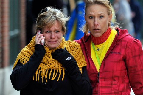 Women react as they walk from the site of an explosion during the Boston Marathon in Boston, April 15, 2013.