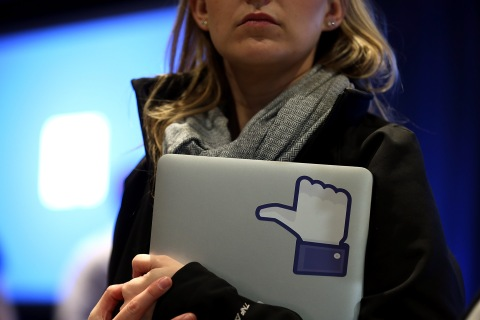 "A Facebook employee holds a laptop with a ""like"" sticker on it at an event at Facebook headquarters in Menlo Park, Calif., on April 4, 2013."