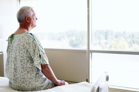 Senior male patient sitting on bed looking out window in room of hospital