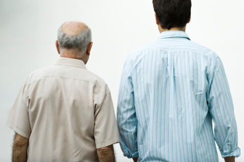 Senior man walking with adult son, rear view
