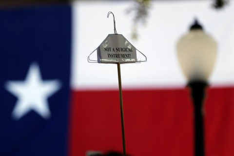 A protester holds up their message on a hangar during a rally against new abortion legislation, Monday, July 1, 2013, in Austin, Texas.