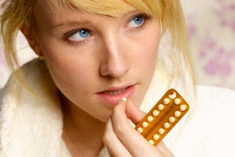 Teenager taking birth control pill.