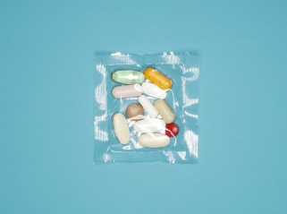 Sealed plastic packet of pills on blue background