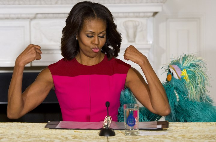 First Lady Michelle Obama flexes her muscles alongside Sesame Street character Rosita