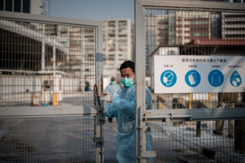 A security guard closes the gate of a live poultry market in Cheung Sha Wan before officials proceed to cull chickens in Hong Kong on Jan. 28, 2014.